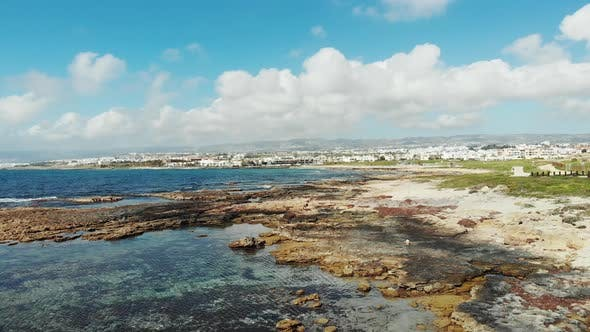 Thumbnail for Drone view of sea coast with waves hitting rocky beach. Mountains and city buildings in Background.