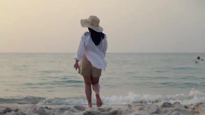 Woman walking on the beach beautiful sunset.