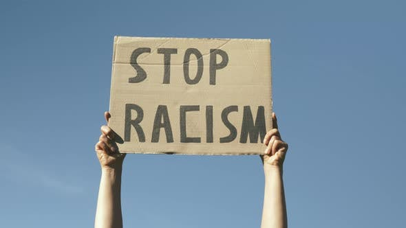 """Woman hands hold poster Stop Racism. Sign """"Stop Racism""""against blue sky."""