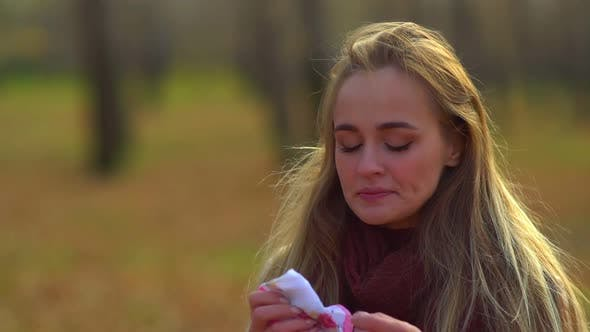 Young Attractive Girl Sneezes and Blows her Nose in a White Napkin