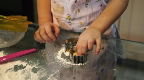 Child making cut-out cookies
