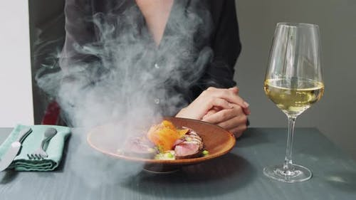 Waiter Serving Meat Dishes with Smoke To a Client in a Restaurant