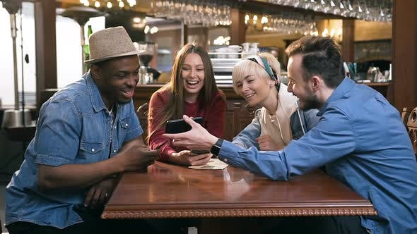 Thumbnail for Four happy Caucasian Friends Using Smart Phone Together in the Bar, Pub