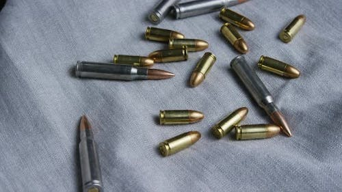 Cinematic rotating shot of bullets on a fabric surface - BULLETS 088