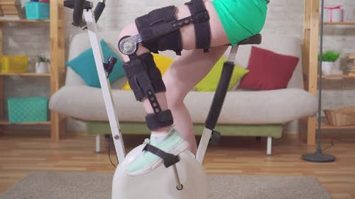 Young Woman Knee Bend Orthosis Knee Brace After Injury on a Stationary Bike Knee Bend Orthosis Knee