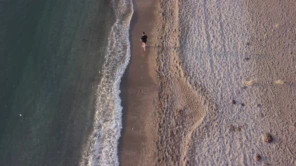 Thumbnail for Young man running at shore alone. Top view, Aerial view