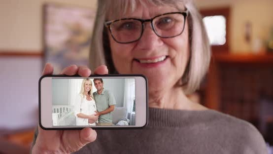 Thumbnail for Close-up of old lady holding phone with pregnant daughter and husband on screen