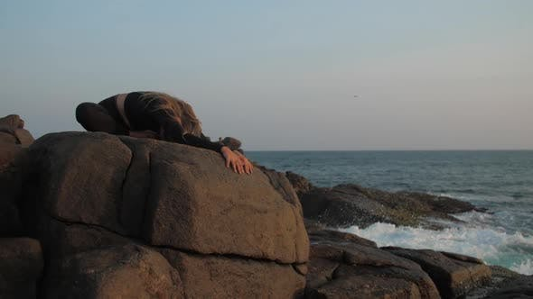 Thumbnail for Young Woman in Black Tracksuit Stretches on Grey Rocky Cliff