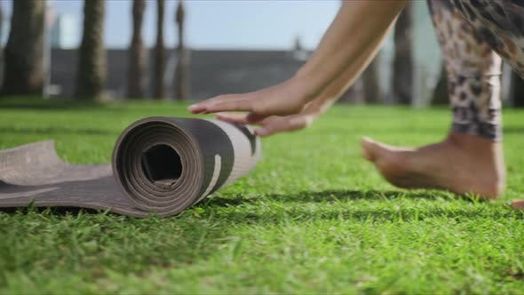 Woman Hands Rolling Up Yoga Mat After Training in park.Girl Folding Mat on Grass
