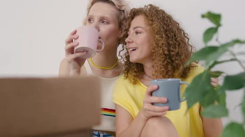 Women Sitting On The Floor While Drinking Coffee