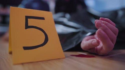Nahaufnahme des Zeichens mit Nummer fünf, die neben der weiblichen kaukasischen Hand im Blutbad steht. Kriminalität