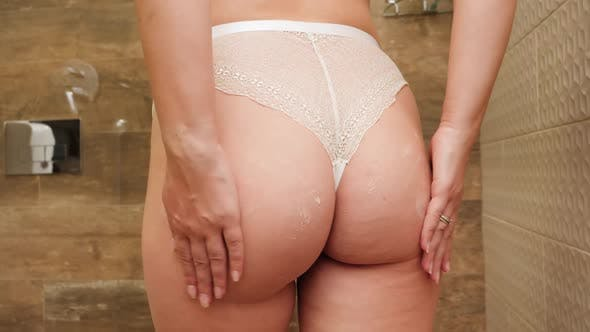 Rear View of Sexy Young Woman in Lace Panties Massaging Her Buttocks and Applying Anti Cellulite