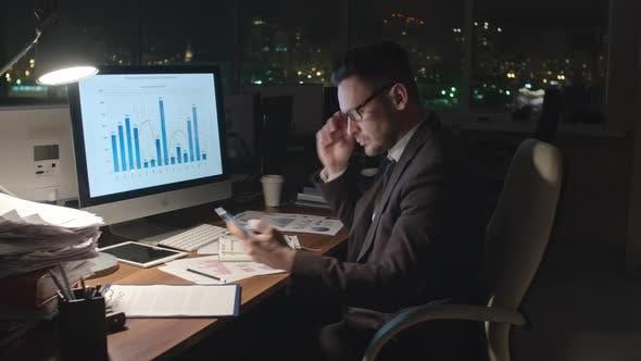 Thumbnail for Businessman Analyzing Statistics at Night