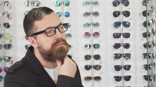 Thumbnail for Bearded Mature Man Rubbing His Beard Thoughtfully Choosing New Glasses