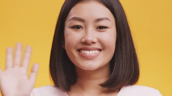 Thumbnail for Close Up of Friendly Asian Lady Waving Hand in Hello Gesture and Smiling, Orange Studio Background