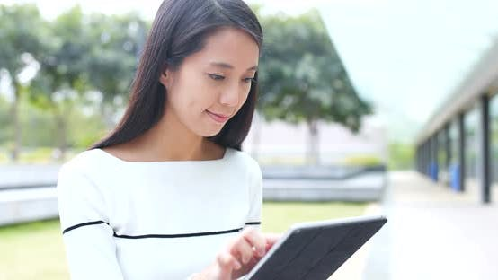 Thumbnail for Woman use of digital tablet computer at outdoor