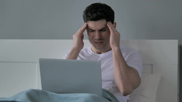 Thumbnail for Headache, Tense Young Man Working on Laptop in Bed