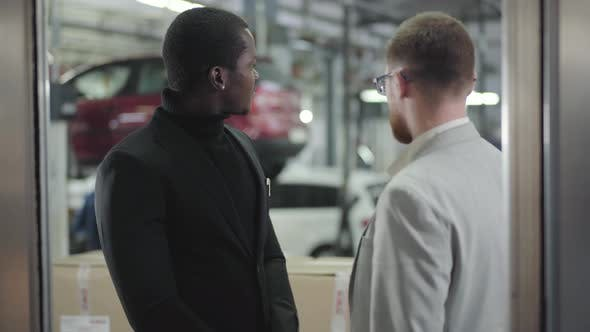 Thumbnail for Portrait of Young Handsome African American Man Talking with Car Dealer in Showroom