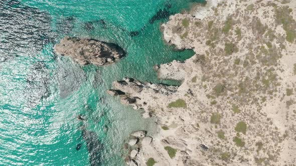 Overhead Top Down Aerial Flight Over Greek Island Milos Turquoise Blue Ocean with Rocky Cliff Coast