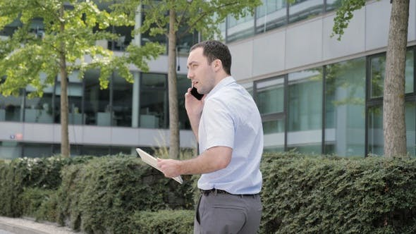 Thumbnail for Man on Phone - young businessman walking using smartphone