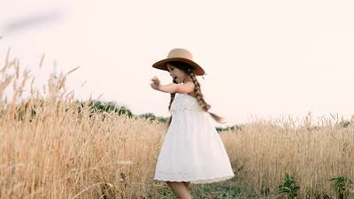 Little Girl is Spinning in a Wheat Field