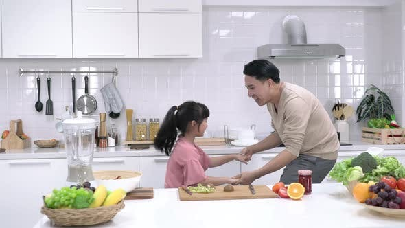 Father and daughter dancing in kitchen