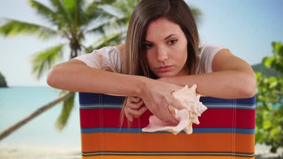 Thumbnail for Lonely millennial female sitting in tropical beach setting holding seashell