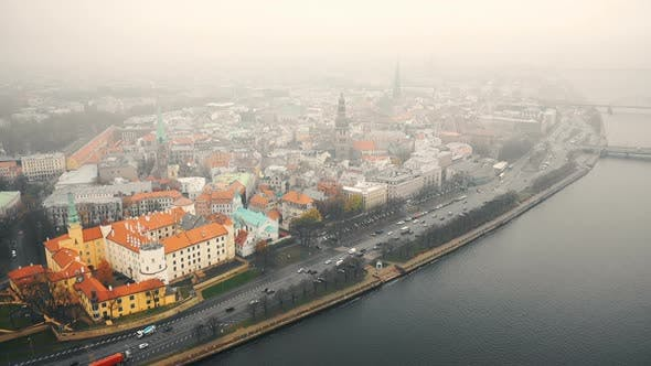 Thumbnail for Amazing Aerial Cityscape Panorama of Riga Old Town and Car Traffic Along River Daugava Under Fog on