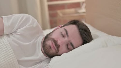 Peaceful Young Male Sleeping in Bed