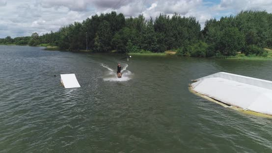 Wakeboarding in a Lake Near the Forest, Sportsman Surfs on the Water, Ride on a Wakeboarding Board