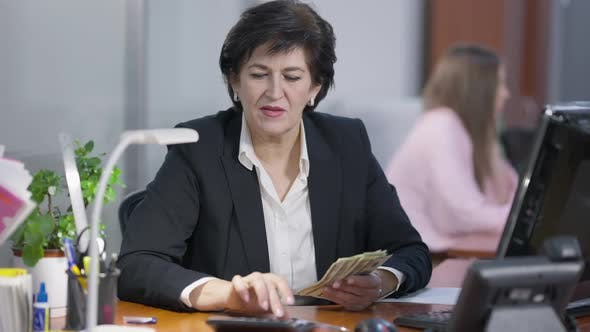 Concentrated Confident Middle Aged Manager Counting Cash Money Using Calculator