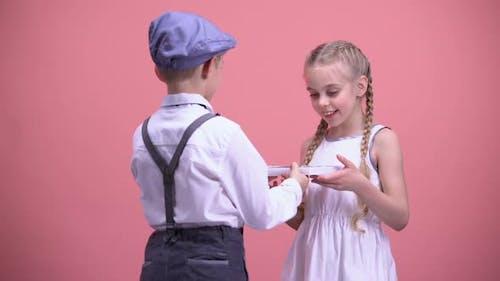 Little Boy Presenting Chocolate Candies to Surprised Girlfriend, Valentines Day