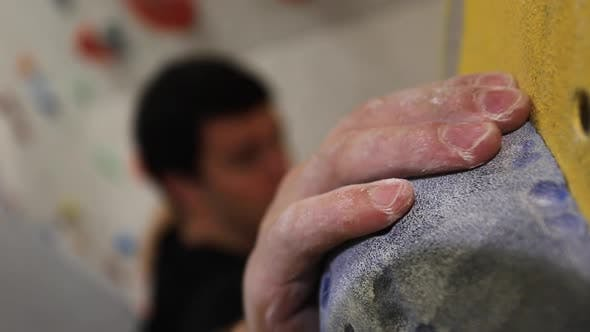Close-up of a mans hands has he climbs in an indoor climbing gym.