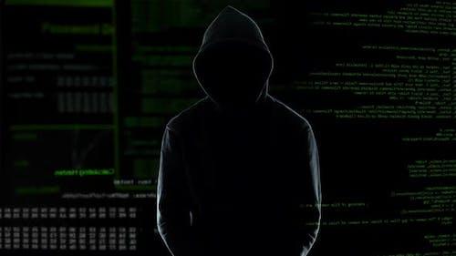 Männlicher Programmierer stehend in Handschellen nach der Begehung von Cyberkriminalität, Strafe