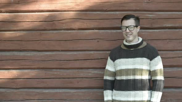 Happy Young Man with Eyeglasses Smiling Against Wooden Wall in Autumn
