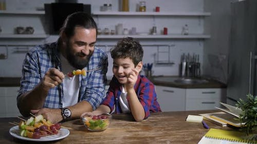 Father and Son Preparing Fruit Skewers in Kitchen