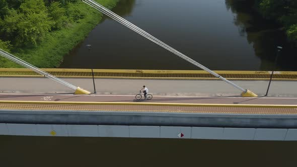Man Rides Bicycle Over the Bridge