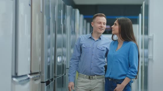 Cover Image for Buying a New Refrigerator. Choosing the Right Model for a Family Couple in an Electronics Store.
