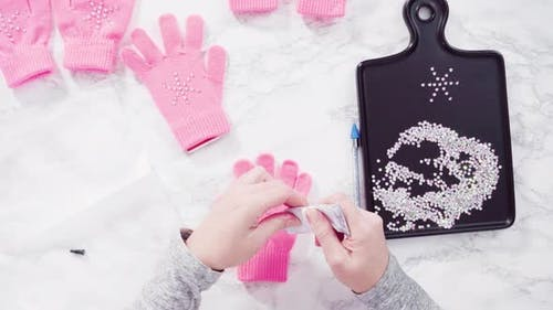 Flat lay. Rhinestone pink kids gloves with snowflake shapes.
