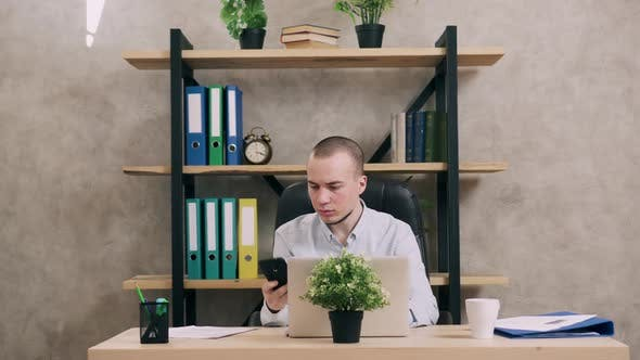 Young Man Doing Paperwork in Office
