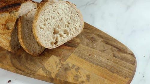Stück frisches Brot fällt auf ein Schneidebrett