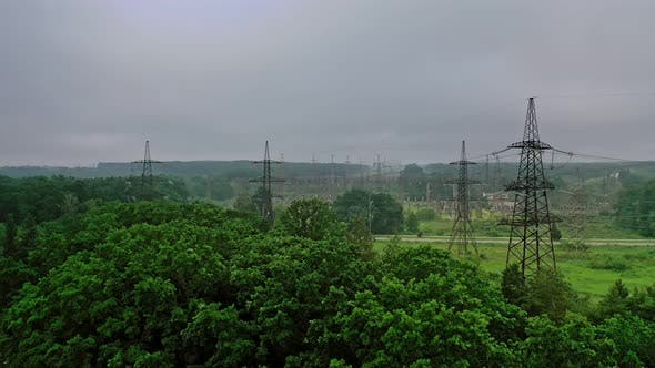 High voltage electricity towers among nature