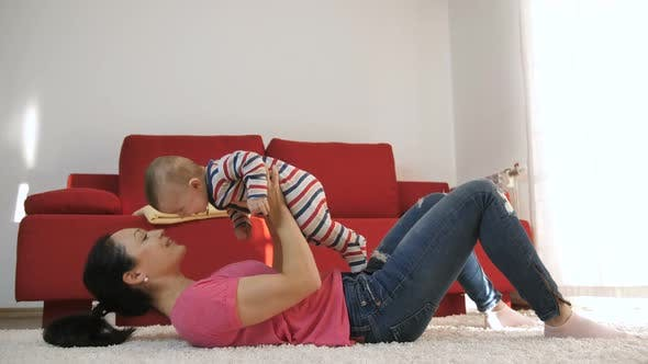 Thumbnail for Mother Playing with Baby Son at Home Lifting Him