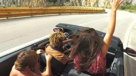 Thumbnail for Group of friends driving on the road along the coast in red convertible