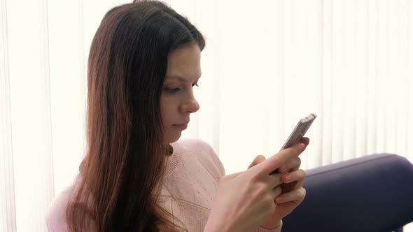 Thumbnail for Young Woman Brunette Is Typing a Message on Her Mobile Phone and Looking at Screen