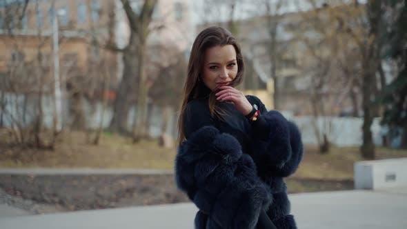 Young beautiful fashionable lady wearing stylish dark fur coat posing in park