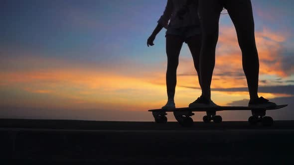 Cover Image for Close-up of the Legs of Two Girls Girlfriend in Shorts and Sneakers Ride Skateboards on the Slope