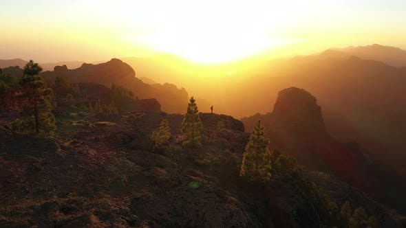 Thumbnail for Man Looking At View As Sun Sets Over Misty Mountains