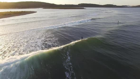 View From a Drone To a SUP Surfer Riding a Wave in the Sea at Sunset