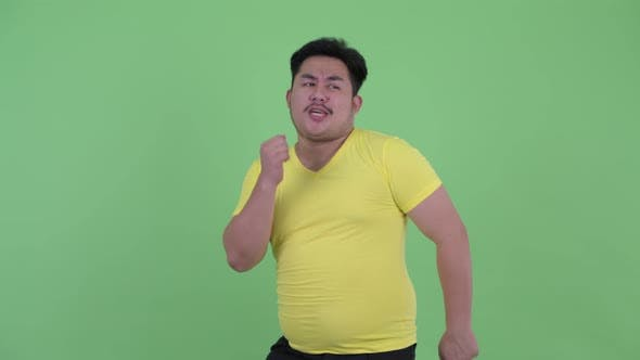 Thumbnail for Happy Young Overweight Asian Man Dancing